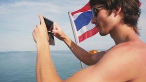 Giovane in occhiali da sole che prendono selfie con la bandiera tailandese mentre navigando sulla nave nel mare Concetto di viagg stock footage