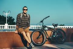 Giovane in occhiali da sole che si siedono sulla fontana accanto alla bicicletta nel concetto di riposo urbano di stile di vita q Fotografia Stock Libera da Diritti