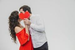 Giovane offerta e nelle coppie di amore Tenga un cuore rosso di carta in vostre mani Durante il questo essi baciare e nascondersi fotografia stock