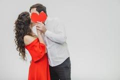 Giovane offerta e nelle coppie di amore Tenga un cuore rosso di carta in vostre mani Durante il questo essi baciare e nascondersi immagini stock libere da diritti