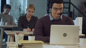 Giovane operaio allegro felice della call center in cuffie che sorride e che lavora al computer portatile video d archivio