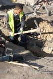 Giovane operaio che scava sul sito della costruzione di strade fotografia stock libera da diritti