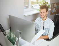 Giovane operaio che si siede in un ufficio al computer Free lance in una camicia bianca Il progettista si siede davanti alla fine Fotografia Stock