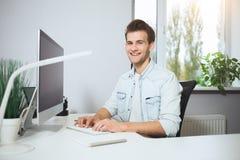 Giovane operaio che si siede in un ufficio al computer Free lance in una camicia bianca Il progettista si siede davanti alla fine Fotografia Stock Libera da Diritti