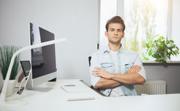 Giovane operaio che si siede in un ufficio al computer Free lance in una camicia bianca Il progettista si siede davanti alla fine Immagini Stock
