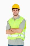 Giovane operaio di costruzione sorridente con le braccia piegate Fotografia Stock