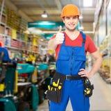 Giovane operaio professionista con i pollici su al negozio Immagini Stock Libere da Diritti
