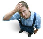 Giovane operaio in vestiti da lavoro, domandantesi ed esitanti. Ha osservato da sopra. fotografia stock