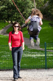 Giovane oscillazione della madre un bambino in campo da giuoco Immagine Stock