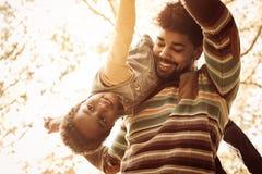 Giovane padre afroamericano in parco che porta sua figlia sulla s fotografia stock