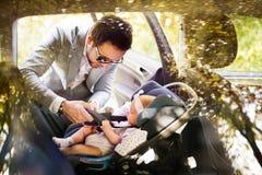 Giovane padre che mette neonata nell'automobile immagini stock