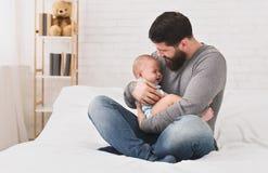 Giovane padre che tiene gridare neonato sveglio sonnolento fotografia stock libera da diritti