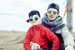Giovane padre con suo figlio divertendosi fuori nel giacimento di primavera, famiglia felice che sorride, la gente di stile di vi fotografia stock