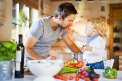 Giovane padre con una cottura del ragazzo del bambino immagini stock