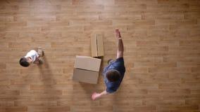 Giovane padre e figlio che entrano nella casa vuota con le scatole, colpo superiore, funzionamento del ragazzino ed abbraccianti  stock footage