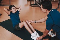 Giovane padre e figlio che fanno gli esercizi nel club di sport immagini stock