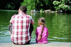 Giovane padre e la sua figlia vicino allo stagno Fotografia Stock Libera da Diritti