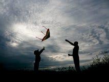 Giovane padre e suo il figlio che pilotano un aquilone al tramonto Fotografia Stock Libera da Diritti