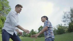 Giovane padre ed i livelli cinque e stringere del ragazzo le mani all'aperto Padre e un bambino divertendosi nel parco person e v video d archivio