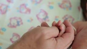 Giovane padre felice che gioca con la mano nell'ospedale, primo piano del suo neonato archivi video
