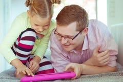 Giovane padre felice divertiresi con il suo spirito di lavoro della piccola figlia fotografia stock libera da diritti
