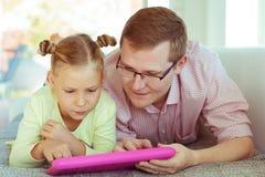 Giovane padre felice divertiresi con il suo spirito di lavoro della piccola figlia immagini stock libere da diritti