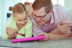Giovane padre felice divertiresi con il suo spirito di lavoro della piccola figlia immagini stock