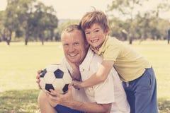 Giovane padre felice e 7 o 8 anni eccitati del figlio che gioca insieme calcio di calcio sul giardino del parco della città che p Fotografia Stock