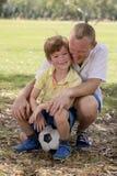 Giovane padre felice e 7 o 8 anni eccitati del figlio che gioca insieme calcio di calcio sul giardino del parco della città che p Fotografia Stock Libera da Diritti