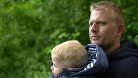 Giovane padre felice e piccolo figlio sveglio che vanno a casa dopo la passeggiata archivi video