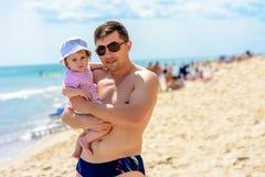 Giovane padre in occhiali da sole sulla spiaggia con una piccola figlia immagine stock libera da diritti