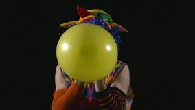 Giovane pagliaccio divertente che gonfia pallone e che lo scoppia video d archivio