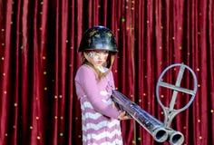 Giovane pagliaccio femminile in casco che tende grande fucile Fotografie Stock