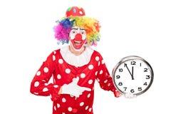 Giovane pagliaccio maschio che tiene un grande orologio di parete Fotografia Stock