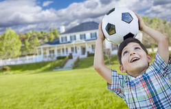 Giovane pallone da calcio sorridente della tenuta del ragazzo davanti alla Camera Fotografia Stock Libera da Diritti