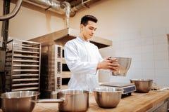 Giovane panettiere abile che mette ciotola con farina sulla scala della cucina fotografie stock libere da diritti