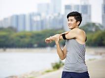 Giovane pareggiatore asiatico che allunga armi prima dell'correre Immagine Stock Libera da Diritti