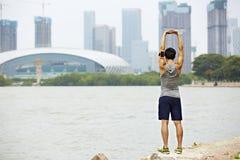 Giovane pareggiatore asiatico che allunga armi prima dell'correre Fotografia Stock Libera da Diritti