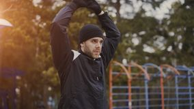 Giovane pareggiatore attraente dell'uomo che si scalda prima dell'correre all'aperto nel parco di inverno Fotografia Stock Libera da Diritti