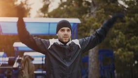 Giovane pareggiatore attraente dell'uomo che si scalda prima dell'correre all'aperto nel parco di inverno Immagini Stock