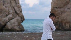 Giovane passeggiata bella dell'uomo vicino al mare ventoso sulla spiaggia fra le rocce cyprus Pafo stock footage