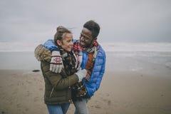 Giovane passeggiata delle coppie lungo la spiaggia di inverno Immagini Stock