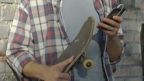 Giovane pattinatore maschio che ascolta la musica in smartphone, amici di chiacchierata, studente stock footage