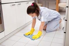 Giovane pavimento di pulizia della domestica fotografie stock