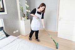 Giovane pavimento di pulizia della domestica con la zazzera a casa, concetto di servizio di pulizia Fotografie Stock Libere da Diritti