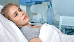 Giovane paziente femminile che si trova in una stanza di ospedale Donna triste e turbata che pensa alla vita in una clinica moder video d archivio