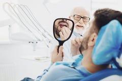 Giovane paziente maschio per quanto riguarda i suoi denti immagini stock libere da diritti