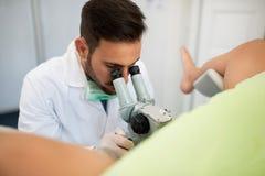Giovane paziente professionale dell'esame del ginecologo con il colposcope fotografia stock libera da diritti