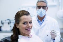 Giovane paziente sorridente che si siede sulla sedia del dentista Fotografie Stock