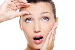Giovane pelle graziosa di compressione della donna sulla fronte Immagine Stock